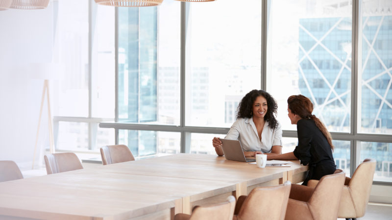 Two Woman Talking at Conference Table
